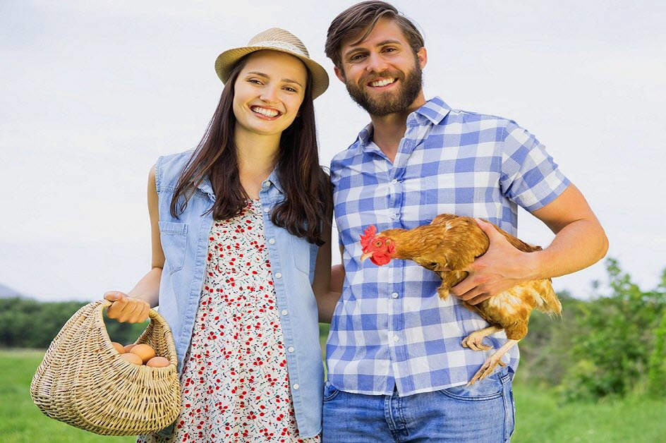 Happy farmer couple with chicken and basket of freshly collected eggs